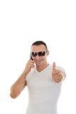 Homem com os óculos de sol no t-shirt branco que responde ao telefone esperto e ao s Imagens de Stock