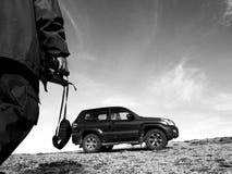 Homem com os binóculos nas montanhas com seu 4x4 Imagens de Stock Royalty Free