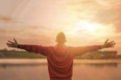 Homem com os braços espalhados olhando montanhas Imagem de Stock