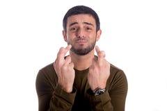 Homem com os dedos cruzados Fotografia de Stock