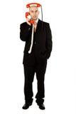 Homem com os monofones vermelhos do telefone Foto de Stock Royalty Free