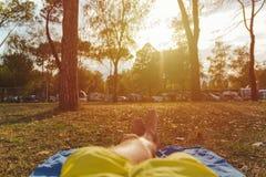 Homem com os pés cruzados que relaxam no prado que olha o acampamento e o por do sol imagem de stock