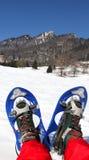 Homem com os sapatos de neve modernos azuis na montanha Imagem de Stock