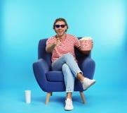 Homem com os vidros 3D, a pipoca e a bebida sentando-se na poltrona durante a mostra do cinema foto de stock