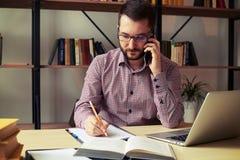 Homem com os vidros que fazem anotações ao falar no telefone fotos de stock