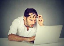 Homem com os vidros que têm os problemas da visão confundidos com o portátil Imagens de Stock Royalty Free