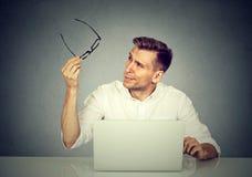 Homem com os vidros que têm os problemas da visão confundidos com o portátil Foto de Stock
