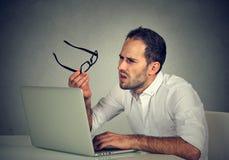 Homem com os vidros que têm os problemas da visão confundidos com o portátil Fotos de Stock Royalty Free