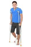 Homem com pé quebrado usando a muleta Foto de Stock
