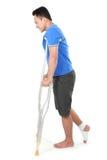 Homem com pé quebrado usando a muleta Fotos de Stock