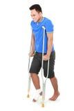 Homem com pé quebrado usando a muleta Imagem de Stock