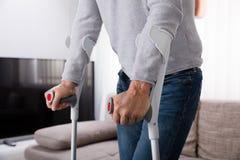 Homem com pé quebrado usando muletas foto de stock