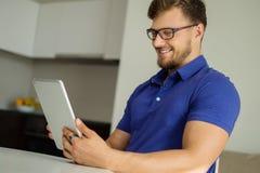 Homem com PC da tabuleta em casa Foto de Stock Royalty Free
