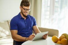 Homem com PC da tabuleta em casa Fotografia de Stock Royalty Free