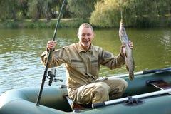 Homem com pesca da haste e da captura do barco fotografia de stock