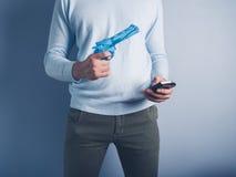 Homem com pistola de água e o telefone esperto Imagem de Stock