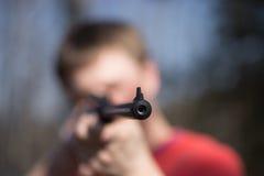 Homem com a pistola pneumática na floresta Fotografia de Stock