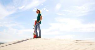 Homem com a placa da areia que olha uma distância no deserto 4k video estoque