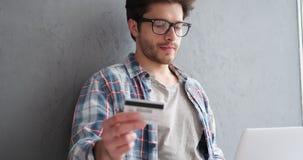 Homem com portátil e cartão de crédito em casa vídeos de arquivo