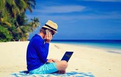 Homem com portátil e telefone celular na praia tropical Imagem de Stock Royalty Free