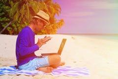 Homem com portátil e telefone celular na praia tropical Fotos de Stock Royalty Free