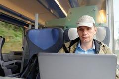 Homem com portátil em um trem imagens de stock royalty free