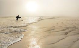 Homem com a prancha na praia nevoenta bonita foto de stock