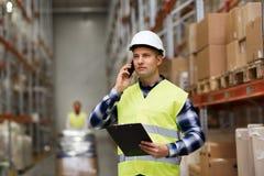 Homem com prancheta e smartphone no armazém Foto de Stock