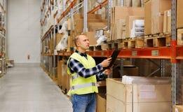 Homem com a prancheta na veste da segurança no armazém Imagens de Stock