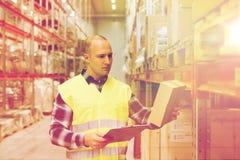 Homem com a prancheta na veste da segurança no armazém Imagem de Stock