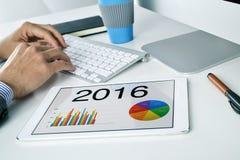 Homem com a previsão econômica para 2016 em sua tabuleta fotografia de stock royalty free