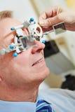 Homem com quadro experimental no óptico fotos de stock