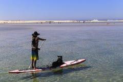 Homem com seu cão em uma placa, stephens do porto, Austrália Fotografia de Stock