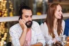 Homem com smartphone e amigos no restaurante imagens de stock royalty free