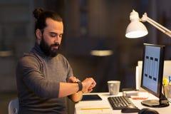 Homem com smartwatch e computador no escritório da noite Imagem de Stock
