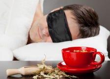 Homem com sono da máscara do sono na cama Fotografia de Stock