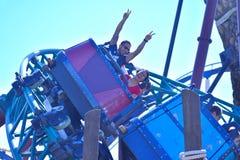 Homem com suas mãos acima e mulher que aprecia o passeio do roller coaster em jardins Tampa Bay de Bush imagem de stock