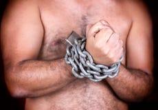 Homem com suas mãos acorrentadas com correntes e um cadeado Foto de Stock