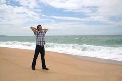 Homem com suas mãos atrás da cabeça na praia imagens de stock
