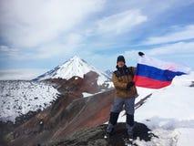Homem com suportes da bandeira do russo pela cratera do vulcão ativo imagens de stock royalty free