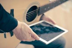 Homem com tabuleta e guitarra Foto de Stock Royalty Free