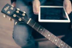 Homem com tabuleta e guitarra Imagens de Stock Royalty Free
