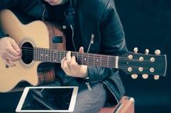 Homem com tabuleta e guitarra Imagem de Stock Royalty Free