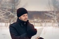 Homem com tabuleta fora na decoração do inverno Foto de Stock Royalty Free