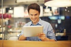 Homem com a tabuleta no café Imagens de Stock Royalty Free