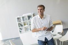 Homem com a tabuleta no escritório Imagem de Stock Royalty Free