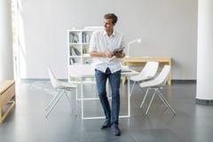 Homem com a tabuleta no escritório foto de stock