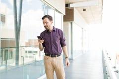 Homem com telefone celular que verifica a aplicação do Internet na compra imagem de stock