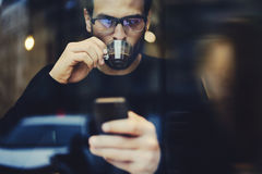 Homem com telefone celular usando a conexão a Internet sem fio para confirmar ou o melhoramento enviado Fotografia de Stock
