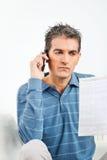 Homem com telefone de pilha e conta de telefone Foto de Stock Royalty Free